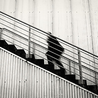 A sinister looking man in black running up stairs against a corrigated wall.