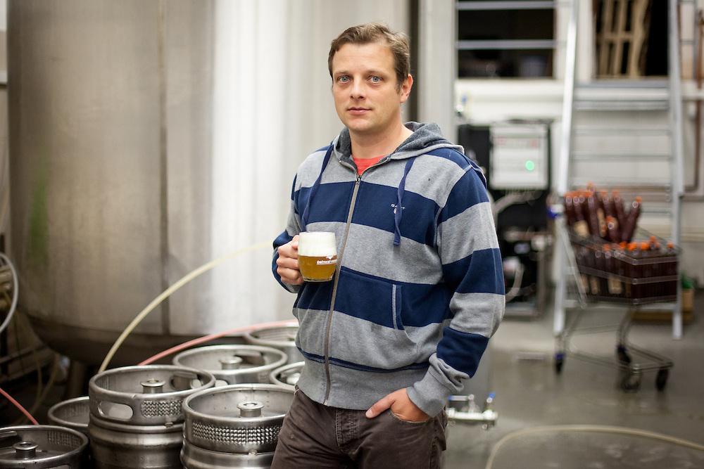 Direktor der Kleinbrauerei in Unetice Herr Ing. Stepan Tkadlec mit einem selbstgebrautem  Bier vor Bierfässern und einem Braukessel im Lagerraum der Brauerei.