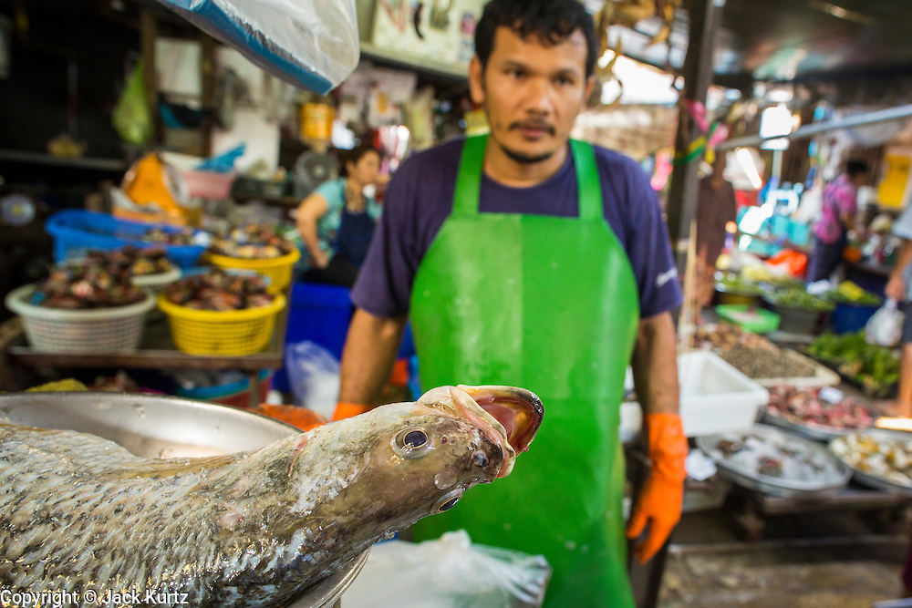 17 JANUARY 2013 - SAMUT SONGKHRAM, SAMUT SONGKHRAM, THAILAND:  A fish monger in the Samut Songkhram market. Four trains each day make the round trip from Baan Laem, near Samut Sakhon, to Samut Songkhram, the train chugs through market eight times a day (coming and going). Each time market vendors pick up their merchandise and clear the track for the train, only to set up again when the train passes. The market on the train tracks has become a tourist attraction in this part of Thailand and many tourists stop to see the train on their way to or from the floating market in Damnoen Saduak.    PHOTO BY JACK KURTZ