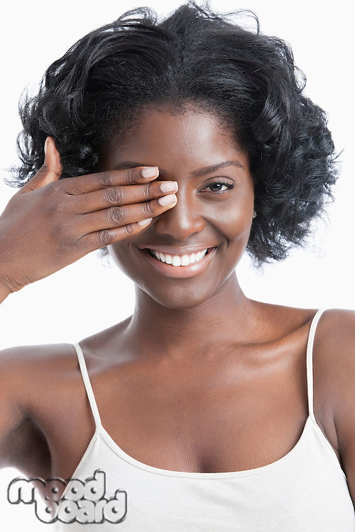 Portrait of a playful young woman with hand over eye against white background