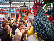 01 FEBRUARY 2017 - BANGKOK, THAILAND:  People pray at a statue of a rooster during Lunar New Year observances at the Poh Teck Tung Shrine in Bangkok. This is the Year of the Rooster in the Chinese zodiac and people pray and make merit to large statues of roosters in Chinese temples and shrines.    PHOTO BY JACK KURTZ