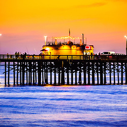 Picture of Balboa Pier at Sunset in Newport Beach California. Balboa Pier is located along the Pacific Ocean Balboa Peninsula in Orange County Southern California. The pier is a popular attraction for fishing and the Ruby's Diner restaurant at the end of the pier.