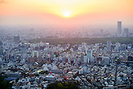 View over Tokyo at sunset. The urban sprawl of the capital city of Japan, looking west from Roppongi Hills to Yoyogi Park  the orange glow of the setting sun at dusk. Japan.