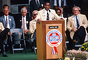 Former NFL players and coaches look on as former Dallas Cowboys running back Tony Dorsett speaks at the podium during his induction speech at his Pro Football Hall of Fame induction ceremony prior to the 1994 NFL preseason football game featuring the San Diego Chargers against the Atlanta Falcons on July 30, 1994 in Canton, Ohio. The Falcons won the game 21-17. (©Paul Anthony Spinelli)