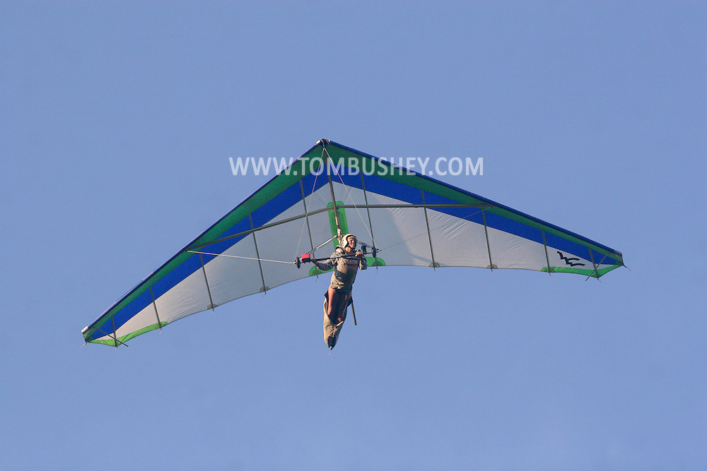 Ellenville, NY - A woman flying a hang glider soars above Ellenville on May 30, 2009.