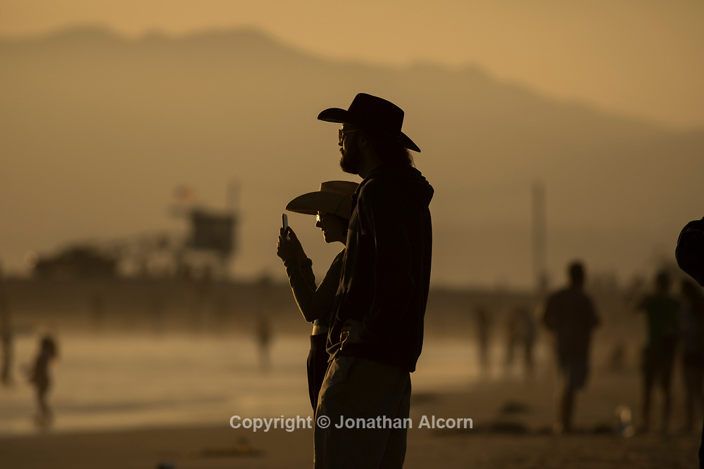 People watch the sunset on Venice Beach