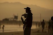 People watch the sunset on Venice Beach