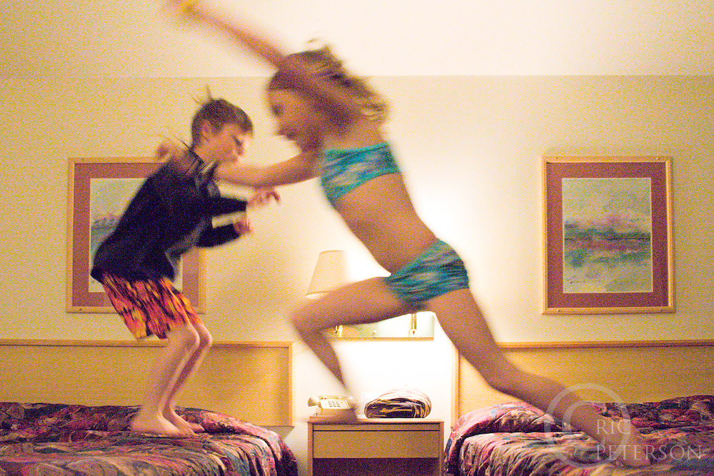 Children jumping on beds in hotel room