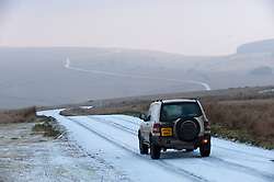 © Licensed to London News Pictures. 22/01/2017. Builth Wells, Powys, Wales, UK. A car drives along a snowy road on the Mynydd Epynt moorland after a light snow fall in the early hours this morning in Powys, Wales, UK. Photo credit: Graham M. Lawrence/LNP