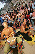 Older hippy men drumming, as a crowd of people look on, Sunset beach party, Benirras Beach, Ibiza, July 2006