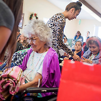 121914       Cable Hoover<br /> <br /> Kyra Spencer helps resident Marie Watchman, right, unwrap her Christmas gifts Friday at McKinley Manor in Gallup. Spencer and other students from the Gallup High School Navajo Government class volunteered to hand out gifts and sing carols to the residents.