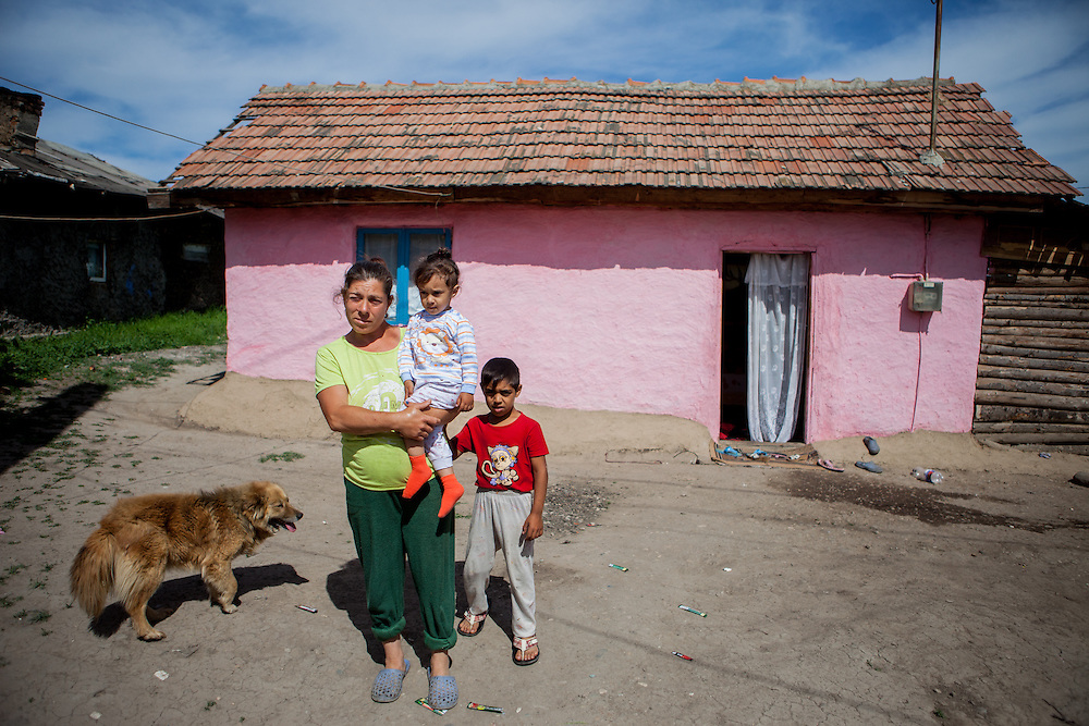 Mother with two children and dog in front of their house in the Roma area of Frumusani.