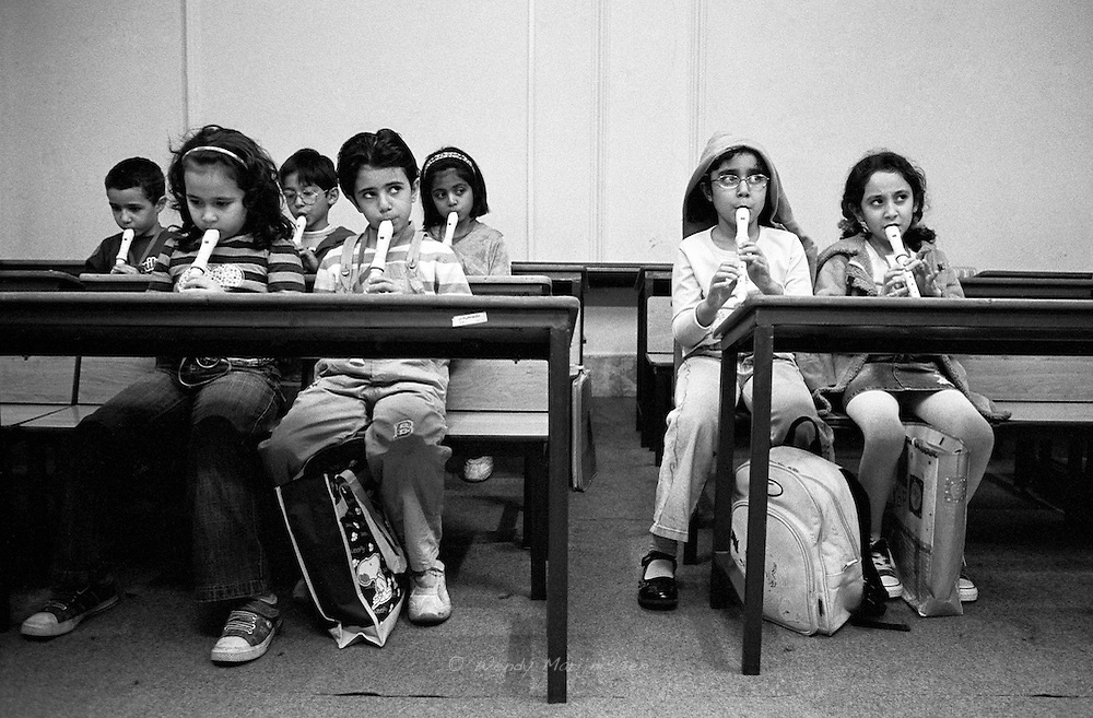 Iranian boys and girls are learning to play the flute in a music school. Tehran, Iran, 2007