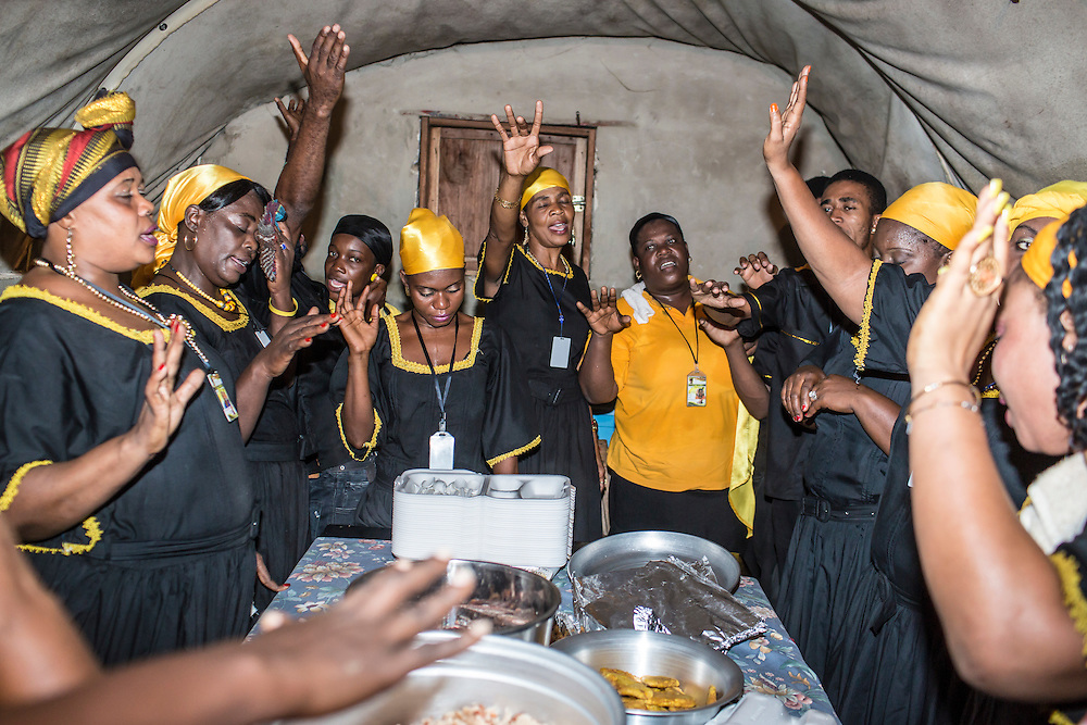 Members of the Societe Ti Pilon Baka vodou troupe pray over food following an annual nighttime ceremony on Sunday, December 14, 2014 in Leogane, Haiti. The city of Leogane, about 20 miles west of Port-au-Prince, was the closest city to the epicenter of the 2010 earthquake, and damage there was extensive.