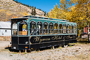 An old street car advertises Wyman Hotel & Inn in Silverton, Colorado, USA. Silverton is a former silver mining camp, now the federally-designated Silverton Historic District. Durango is linked to Silverton by the Durango and Silverton Narrow Gauge Railroad, a National Historic Landmark. Silverton no longer has active mining, but subsists on tourism, maintenance of US 550 (which links Montrose with Durango), mine pollution remediation, and retirees.