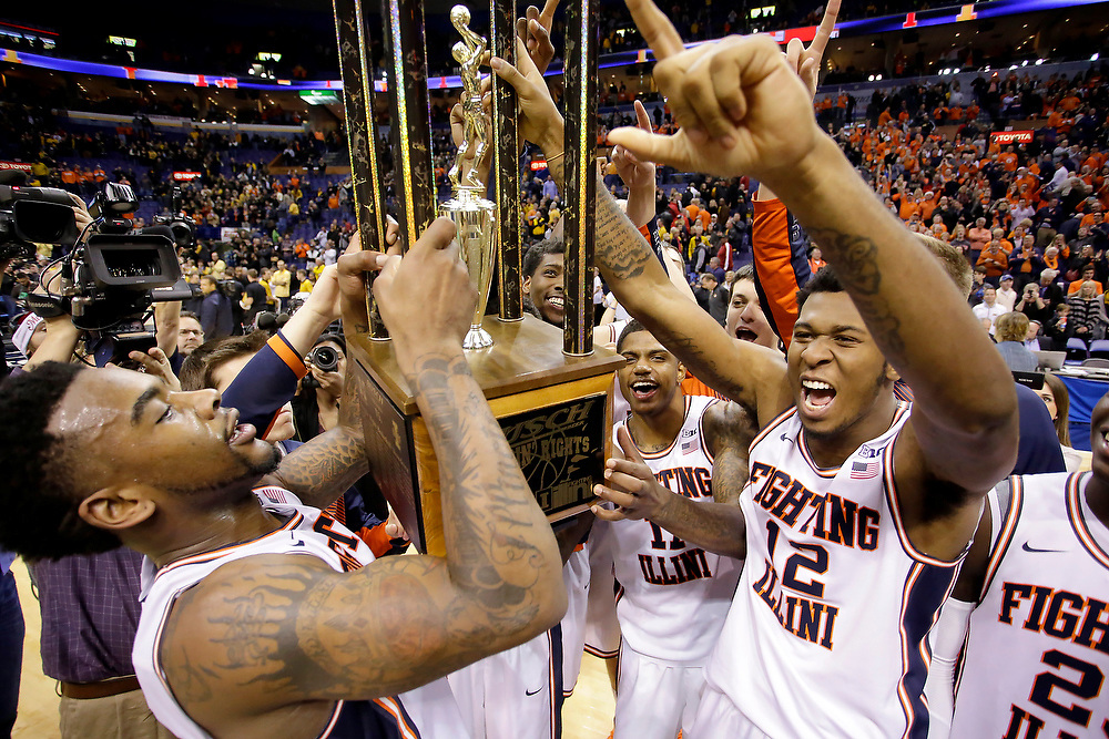 Illinois teammates celebrate with the trophy at the end of the annual Braggin' Rights game against Missouri at the Scottrade Center Saturday, Dec. 20, 2014, in St. Louis. Illinois won the game 62-59. (For the Herald & Review/ Stephen Haas)