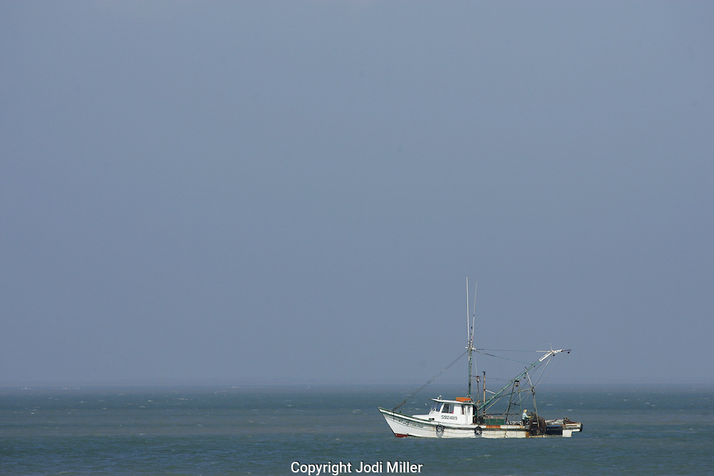 A fishing boat sits in the bay fishing for oysters.