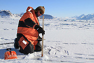 Ice physicist Sebastian Gerland (Norwegian Polar Institute)  works atop fjord ice collecting data about the ice and its role in the carbon cycle; Kongsfjord, Svalbard, Norway.