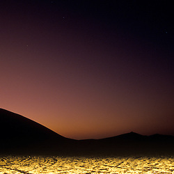 Stars in a dusk sky over the sand dunes of the Namib-Naukluft Park illuminated by car headlights, near Swakopmund, Namibia, Africa