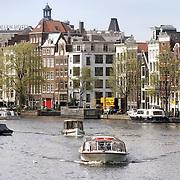 Nederland Amsterdam 26 april 2006 20060426 Foto: David Rozing Stadsgezicht Amsterdam fietsen met op de avoorgrond rondvaartboot en achtergrond grachtenpanden aan het water  Foto David Rozing