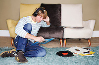 Young Man sitting on shag rug leaning on sofa listening to records