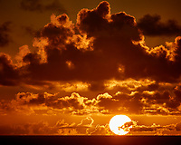 Sun rising through the orange clouds viewed from the aft deck of the MV World Odyssey. Image taken with a Nikon 1 V3  camera and 70-300 mm VR lens (ISO 200, 144 mm, f/8, 1/2000 sec). Raw image processed with Capture One Pro, noise reduction with Topaz DeNoise 5