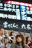 A young woman watches a game of their home baseball team- the Hokkaido Nippon Ham Fighters - at the Sapporo Dome in Sapporo, Hokkaido