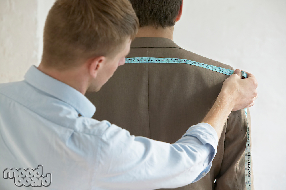 Tailor measuring jacket on man back view close up