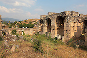 Baths of Hadrian, the largest public baths in Aphrodisias, early 2nd century AD, Aphrodisias, Aydin, Turkey. The baths are dedicated to Emperor Hadrian, 76-138 AD, and were constructed on the Roman model, with a series of parallel vaulted halls, each serving a different function such as cold room, changing room, hot room. The lower walls were built of huge limestone blocks faced in marble and underground were service corridors and water channels. Aphrodisias was a small ancient Greek city in Caria near the modern-day town of Geyre. It was named after Aphrodite, the Greek goddess of love, who had here her unique cult image, the Aphrodite of Aphrodisias. The city suffered major earthquakes in the 4th and 7th centuries which destroyed most of the ancient structures. Picture by Manuel Cohen