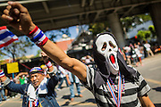 """14 JANUARY 2014 - BANGKOK, THAILAND: An anti-government protestor wearing a mask from the movie """"Scream"""" in front of Royal Thai police headquarters. Hundreds of protestors picketed police headquarters because they accuse the police of siding with the government during the protests. Tens of thousands of Thai anti-government protestors continued to block the streets of Bangkok Tuesday to shut down the Thai capitol. The protest, """"Shutdown Bangkok,"""" is expected to last at least a week. Shutdown Bangkok is organized by People's Democratic Reform Committee (PRDC). It's a continuation of protests that started in early November. There have been shootings almost every night at different protests sites around Bangkok, but so far Shutdown Bangkok has been peaceful. The malls in Bangkok are still open but many other businesses are closed and mass transit is swamped with both protestors and people who had to use mass transit because the roads were blocked.     PHOTO BY JACK KURTZ"""