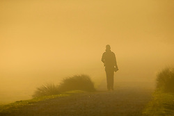 © Licensed to London News Pictures. 26/09/2015. City, UK. A walker at Sunrise on a misty cold Autumn Morning in Richmond Park, London. Photo credit : Ian Schofield/LNP