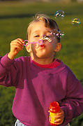 Child (age 3) blowing soap bubbles at the park, Ventura, California