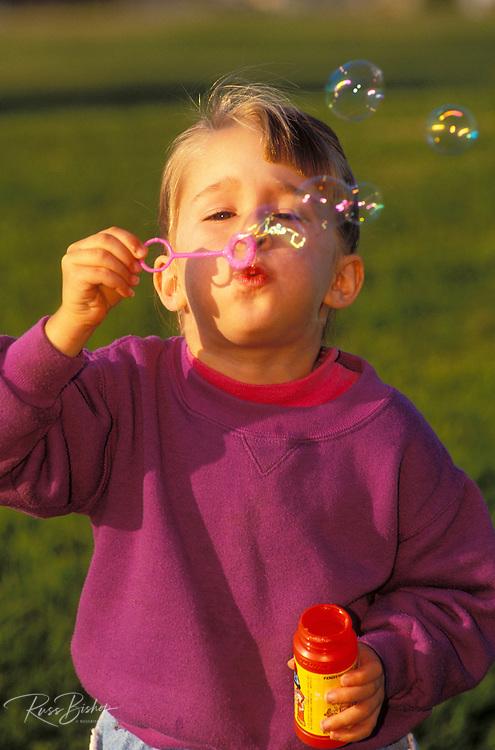 Child (age 3) blowing soap bubbles at the park, Ventura, California