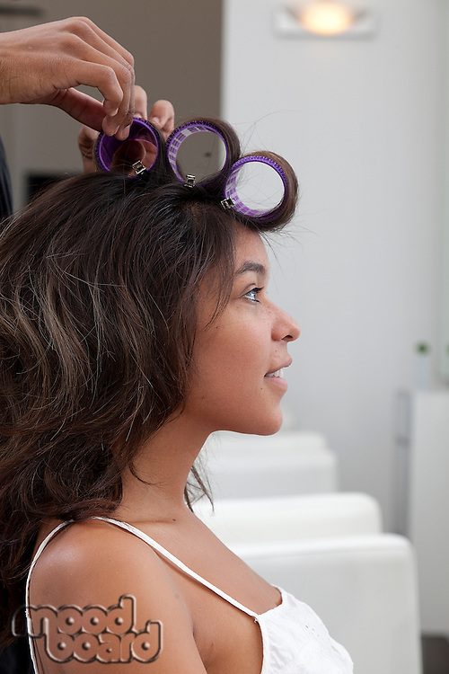 Side profile of young woman wearing curlers
