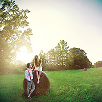young couple on a field, girl sitting on a hay bail as boy flirts