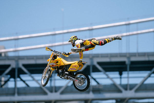 SAN FRANCISCO -  JUNE 25:  Travis Pastrana competes in the 1999 X Games held from June 25, 1999 - July 3, 1999 on Piers 30 & 32 in San Francisco, California.   Pastrana won the Motocross Freestyle event with a record total of 99.0 points.  The San Francisco Bay Bridge is visible in the background. (Photo by David Madison/Getty Images) *** Local Caption *** Travis Pastrana
