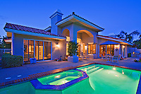 Illuminated swimming pool with Jacuzzi in front of luxury mansion