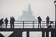 People watching as HMS Dragon sails through the mist into her home port of Portsmouth for the first time in two months.  The Type 45 destroyer has been on a deployment involving exercises with the U.S. Navy and also a visit to the British Overseas Territory of Gibraltar.