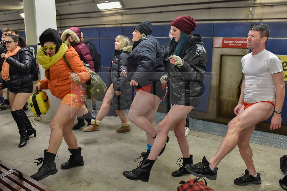 """© Licensed to London News Pictures. 07/01/2018. CHICAGO, USA.  Participants take part in song and dance during the annual """"No Pants Subway Ride"""", a fun event taking place both in Chicago and worldwide, where people ride the subway wearing no trousers.  With Chicago experiencing an extreme cold snap currently, temperatures made taking part more challenging.  Photo credit: Stephen Chung/LNP"""