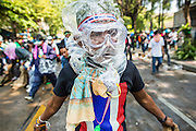 26 DECEMBER 2013 - BANGKOK, THAILAND:  An anti-government protestor wears a plastic bag over his head for protection against tear gas. Thousands of anti-government protestors flooded into the area around the Thai Japan Stadium to try to prevent the drawing of ballot list numbers by the Election Commission, which determines the order in which candidates appear on the ballot of the Feb. 2 election. They were unable to break into the stadium and ballot list draw went as scheduled. The protestors then started throwing rocks and small explosives at police who responded with tear gas and rubber bullets. At least 20 people were hospitalized in the melee and one policeman was reportedly shot by anti-government protestors.     PHOTO BY JACK KURTZ