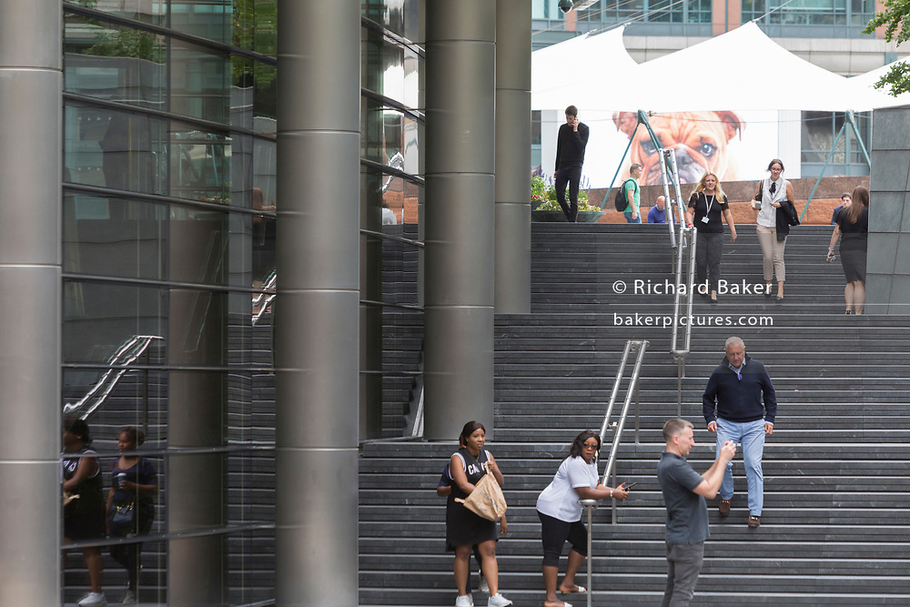 With a British Bulldog on a large screen in the background, Londoners walk up and down steps at Broadgate in the City of London - the capital's financial district - on 20th August 2018, in London, England.