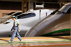 Woman on platform walks past sleek modern bullet trains at Tokyo railway station