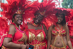 London, August 29th 2016. Three friends, resplendent in their red feather costumes, pose for the camera during day two of Europe's biggest street party, the Notting Hill Carnival.
