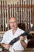Portrait of a mature gun merchant with rifle