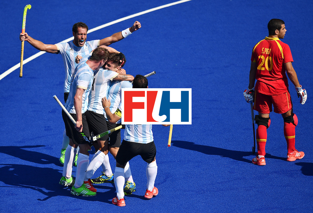 Argentina's players celebrate beside Spain's Salvador Piera (R) during the men's quarterfinal field hockey Spain vs Argentina match of the Rio 2016 Olympics Games at the Olympic Hockey Centre in Rio de Janeiro on August 14, 2016. / AFP / MANAN VATSYAYANA        (Photo credit should read MANAN VATSYAYANA/AFP/Getty Images)