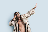 Young man in fur coat looking up with arms raised against light blue background