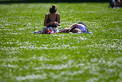 Two women enjoy the warm sunshine among the daisies on a perfect spring day in Regents Park. London, May 04 2018.