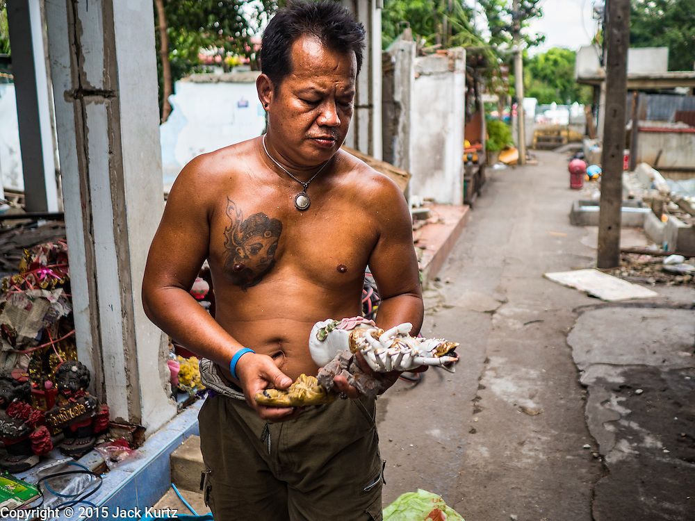 16 NOVEMBER 2015 - BANGKOK, THAILAND:  A scavenger with religious statues he found in an abandoned home in the Wat Kalayanamit neighborhood. Fifty-four homes around Wat Kalayanamit, a historic Buddhist temple on the Chao Phraya River in the Thonburi section of Bangkok, are being razed and the residents evicted to make way for new development at the temple. The abbot of the temple said he was evicting the residents, who have lived on the temple grounds for generations, because their homes are unsafe and because he wants to improve the temple grounds. The evictions are a part of a Bangkok trend, especially along the Chao Phraya River and BTS light rail lines. Low income people are being evicted from their long time homes to make way for urban renewal.          PHOTO BY JACK KURTZ