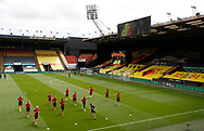 Watford players warm up before the giant banners covering the seats where the fans would sit during the Premier League match at Vicarage Road, Watford. Picture date: 20th June 2020. Picture credit should read: Darren Staples/Sportimage