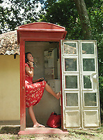 Young woman using pay phone standing on one leg
